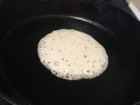 making semolina yeast pancakes in iron pan