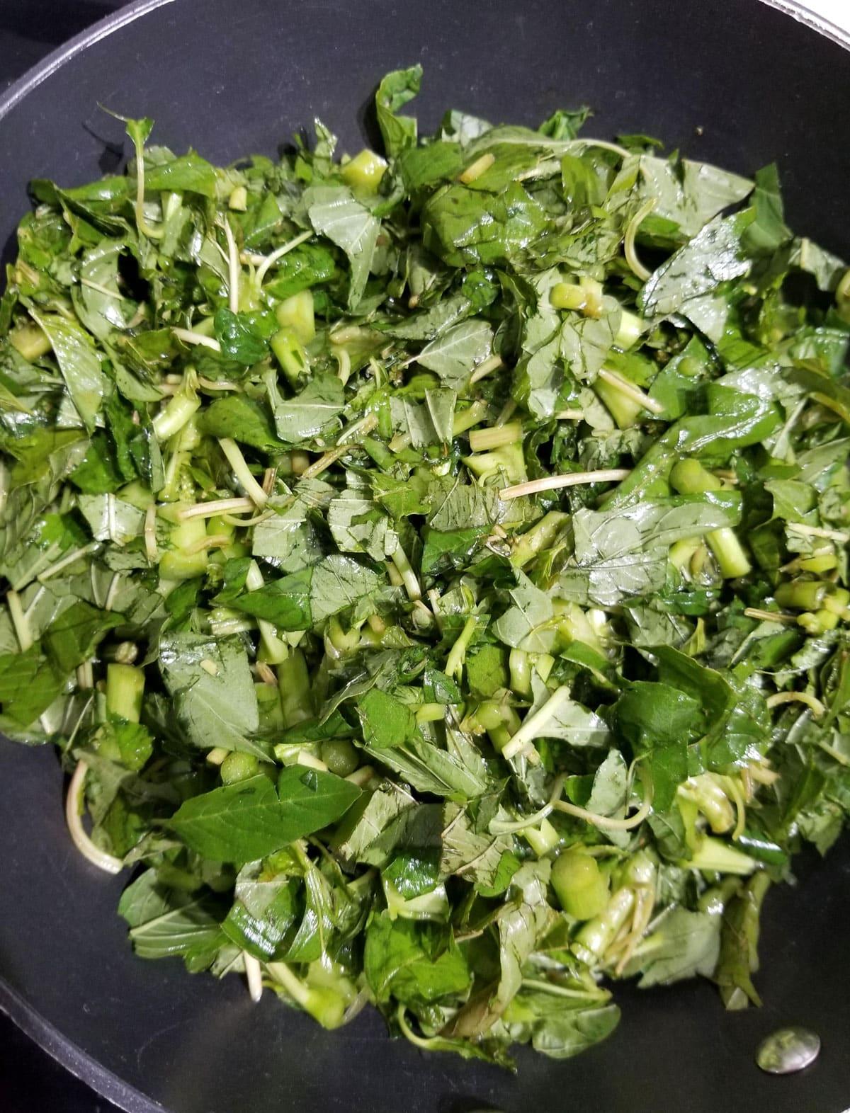 cooking amaranth leaves in pan or skillet